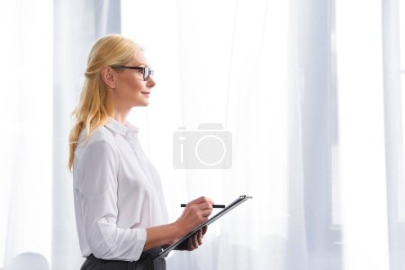 Photo for Side view of female psychologist in eyeglasses writing in clipboard - Royalty Free Image