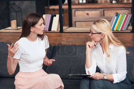 side view of woman gesturing by hands and talking to female counselor at office