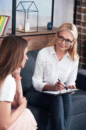 Photo pour Femme stressée assise en session avec une thérapeute au bureau - image libre de droit