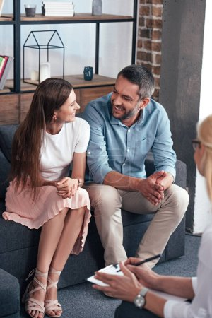 smiling couple looking at each other and sitting on therapy session by female counselor in office
