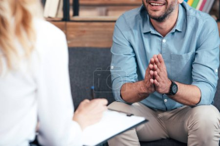 Photo for Cropped image of female counselor writing in clipboard and smiling male holding hand palms together during therapy session in office - Royalty Free Image