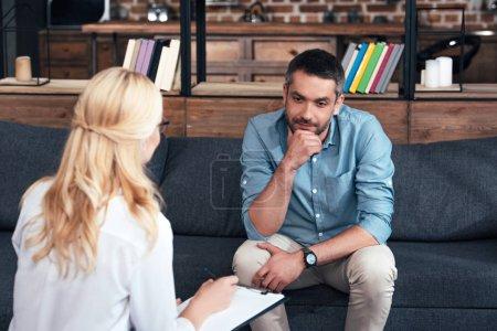 Photo pour Vue arrière de la conseillère écrivant dans le presse-papiers et parlant à un patient masculin au bureau - image libre de droit
