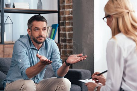 Photo pour Homme d'âge mûr avec larges bras parler à une femme psychiatre à son bureau - image libre de droit