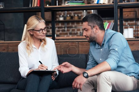man pointing by finger on clipboard of female counselor at office