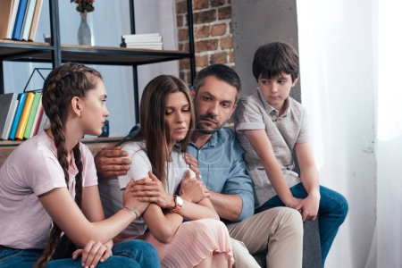 family embracing and cheering up frustrated woman on sofa in counselor office