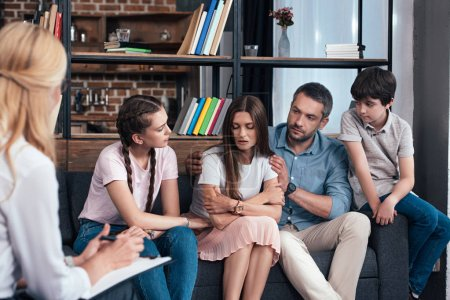 family cheering up woman on therapy session by female counselor in office