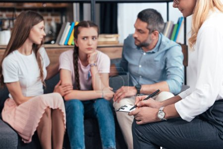Photo pour Image recadrée de conseillère écrivant dans le presse-papiers tandis que les parents encouragent fille sur la session de thérapie - image libre de droit