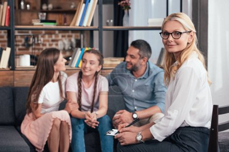 smiling female psychiatrist looking at camera while happy family with daughter on therapy session