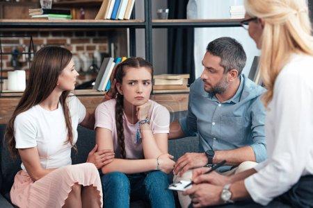 Photo pour Parents encourager fille sur séance de thérapie par une conseillère au bureau - image libre de droit