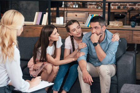 family cheering up man on therapy session by female psychiatrist in office