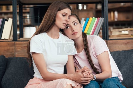 careful teenage girl laying on shoulder of frustrated mother on sofa at home