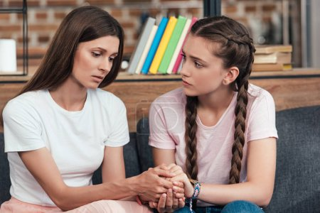 selective focus of teenage girl holding hands of frustrated mother on sofa