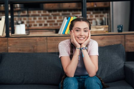 Photo for Smiling teenage girl with hands on cheeks looking at camera and sitting on sofa at home - Royalty Free Image