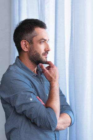 side view of thoughtful man with hand on chin in front of curtains at home