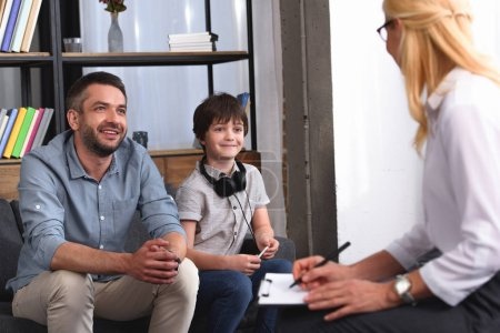 side view of female counselor writing in clipboard while father and son with headphones sitting on therapy session in office