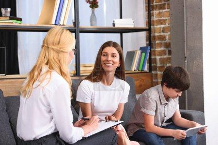 Photo pour Conseillère parlant à une femme souriante pendant que son fils utilise une tablette numérique lors d'une séance de thérapie - image libre de droit