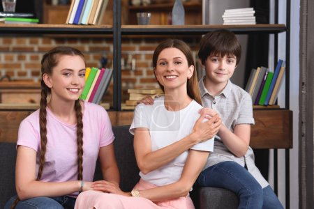 Photo for Happy mother sitting on couch between son and daughter at home - Royalty Free Image