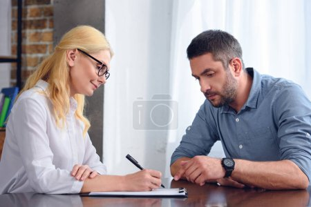 man pointing by finger on clipboard of female psychiatrist while she taking notes at office
