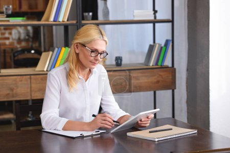 Photo for Focused female counselor in eyeglasses looking at digital tablet screen at table in office - Royalty Free Image
