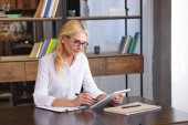 focused female counselor in eyeglasses looking at digital tablet screen at table in office