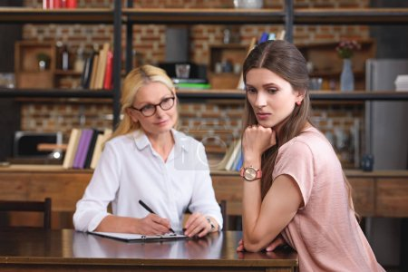 selective focus of stressed woman on therapy session with female counselor in office