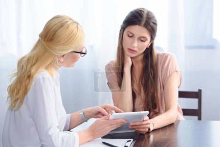 side view of female psychiatrist pointing on digital tablet screen to female patient in office