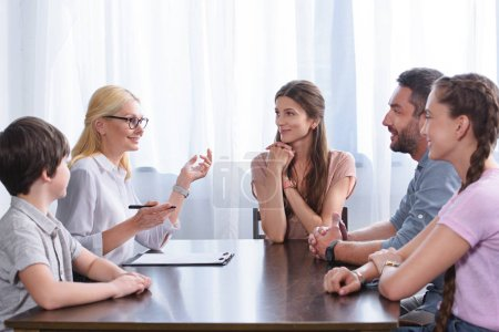 female counselor gesturing by hand and talking to family on therapy session in office