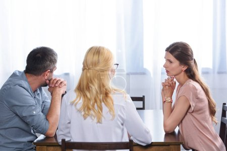 rear view of female psychiatrist talking to couple on therapy session in office
