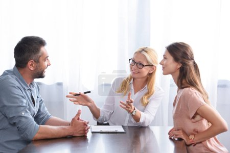 smiling female counselor gesturing by hands and talking to couple on therapy session in office