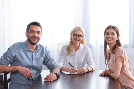 smiling couple and female counselor writing in clipboard at table in office