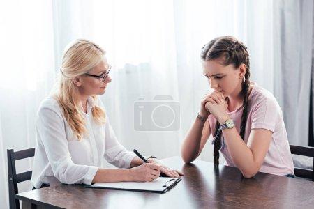 Photo pour Adolescente stressée assise à table sur la séance de thérapie par une conseillère écrivant dans le presse-papiers au bureau - image libre de droit