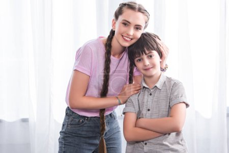 smiling teenage girl embracing little brother with crossed hands at home