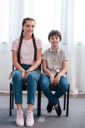 smiling teenage girl with brother sitting on chairs and looking at camera at home