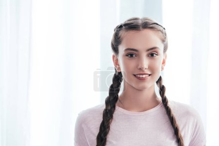 Photo for Portrait of smiling teenage girl with plaits looking at camera in front of curtains at home - Royalty Free Image