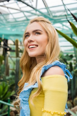 happy young blonde woman in apron looking up in greenhouse