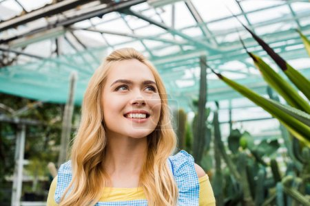beautiful smiling young blonde woman looking up in greenhouse