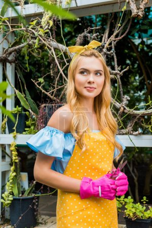beautiful pensive blonde woman in apron and rubber gloves holding scissors and looking away in greenhouse
