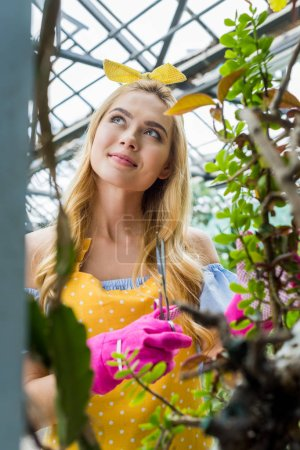 pensive smiling blonde woman in rubber gloves holding scissors and looking away in greenhouse