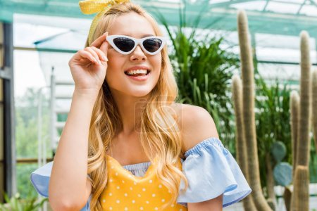 beautiful happy blonde girl in sunglasses and apron smiling in greenhouse