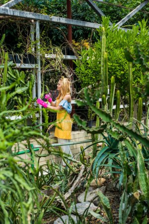 side view of young female gardener working with plants in greenhouse