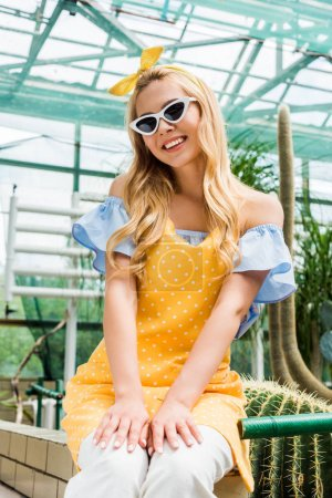 beautiful blonde girl in sunglasses and apron smiling at camera while sitting in greenhouse