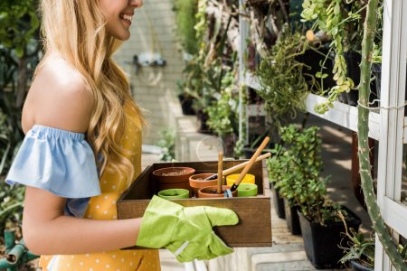 cropped shot of smiling girl holding box with pots, soil and gardening tools