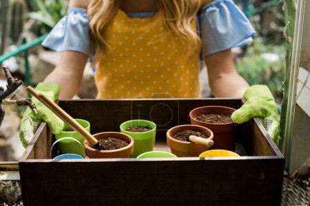 cropped shot of young woman in rubber gloves holding box with pots, soil and gardening tools