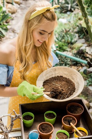 beautiful smiling blonde woman holding bowl with soil and working in greenhouse