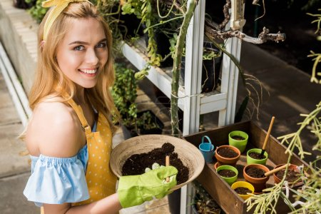 high angle view of beautiful young woman holding bowl with soil and smiling at camera in greenhouse