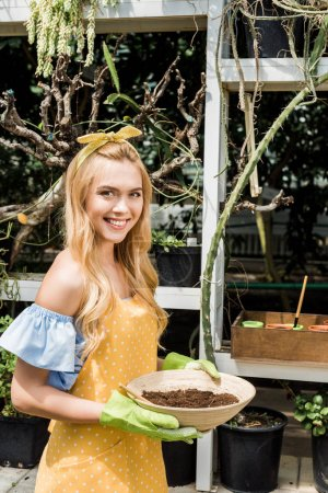 beautiful young woman holding bowl with soil and smiling at camera in greenhouse
