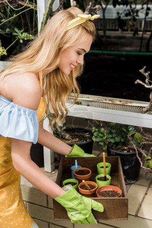 beautiful smiling young woman holding box with pots, soil and gardening tools