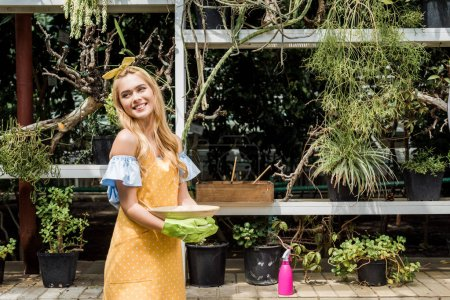 beautiful happy young woman looking away while working in greenhouse