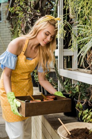 beautiful smiling young woman holding box with flower pots and gardening tools
