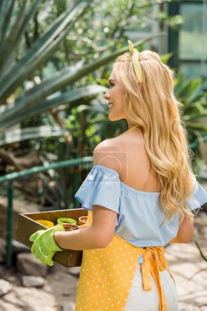 back view of smiling blonde woman holding box with flower pots in greenhouse